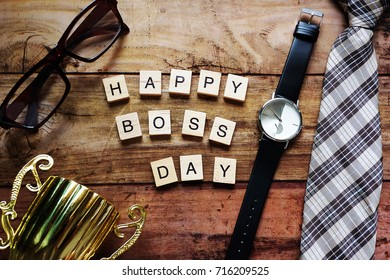 Top view Wood text Happy boss day massage,Necktie,black watch,brown glasses and gold trophy. For concept Happy work Happy Boss and Happy Boss's Day