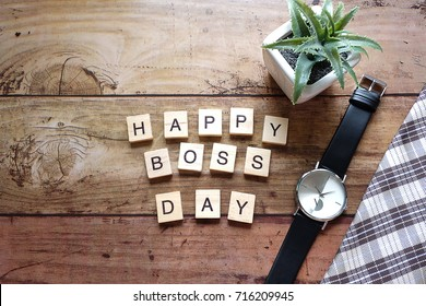 Top view Wood text Happy boss day massage,black watch and green pot plant,For concept Happy work Happy Boss and Happy Boss's Day