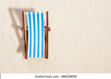 Top view of wooden beach chair on beach.