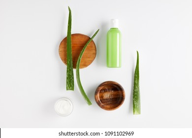 top view of wooden bowl with aloe vera juice, organic cream and shower gel, aloe vera leaves on wooden slices