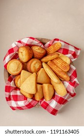 Top View of Wooden Bowl with Homemade Cornbread Muffins, Slices and Sticks on a Neutral Background; Red & White Checked Napkin