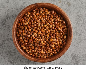 Top view of wooden bowl of salted fried soy beans, isolated on grey background