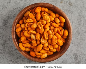 Top view of wooden bowl of salted peanuts, isolated on grey background