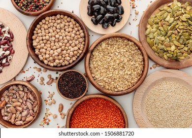 top view of wooden bowls with diverse beans, oatmeal, red lentil, peppercorns, pumpkin seeds and chickpea on white marble surface with scattered grains
