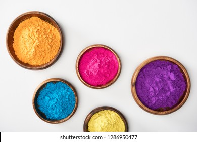 top view of wooden bowls with pink, blue, yellow, purple and orange holi powder on white background