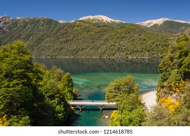 Top view of the wooden bridge on Correntoso river and lake, with turquoise color water, the mountains, forest and blue sky on the background,and the yellow brooms in bloom,on a spring summer sunny day