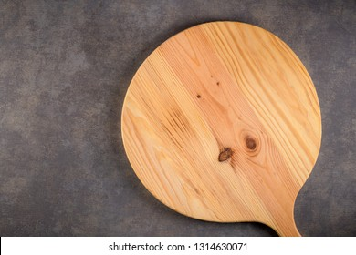 Top view of wooden cutting board on old concrete countertop.