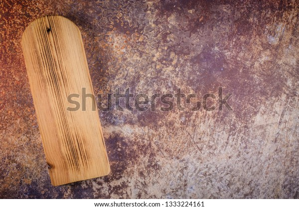 Top view of wooden cutting board on old rusty metal countertop.