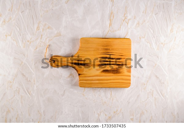 Top view of wooden cutting board on a gray marble background with space for text.