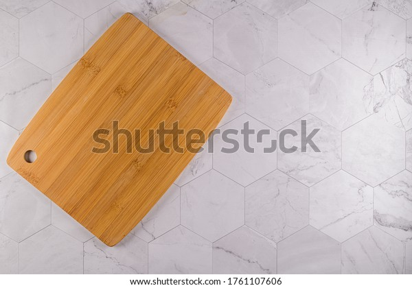 Top view of wooden cutting board on modern hexagonal pattern marble stone countertop.