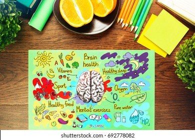 Top view of wooden desk with healthy brainstorm sketch and supplies. Food for brain concept