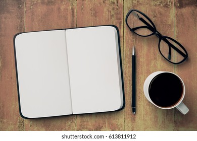 Top view of wooden desktop with open copybook, coffee mug, pen and glasses. Copy space for text. 3D Rendering