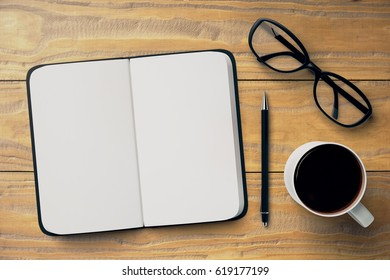 Top view of wooden desktop with open notepad, coffee mug, pen and glasses. Copy space for text. 3D Rendering