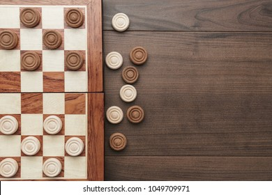 top view of wooden draughts game on brown table background