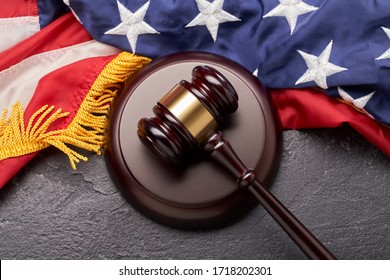 Top view of wooden judge gavel on background of American flag on black background