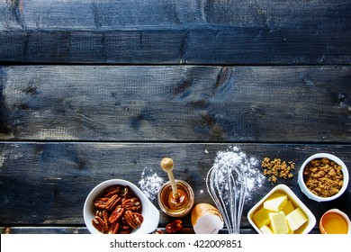 Top view of wooden kitchen table with various ingredients for baking cake (white flour, butter, brown sugar, eggs, honey and nuts) over rustic background, copy space. Dark rural style.