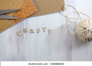 Top view of wooden letters word crafty with thread, cork, cardboard, burlap and scissors over wooden background with copy space