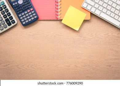 Top view wooden office table with blank desk space. Color paper book, keyboard, calculator and yellow sticky note on top side. Mockup background for announcement concept, vintage and retro styles.