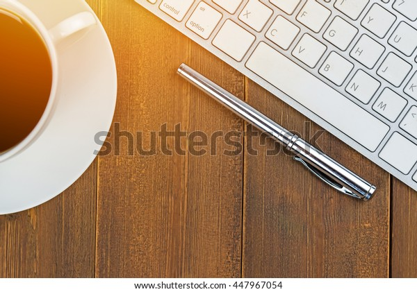 Top view of wooden office table with coffee, keyboard and pen. sunlight filter effect