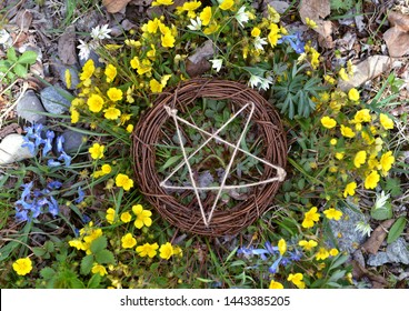Top view of wooden pentagram in grass and flowers. Wicca, esoteric, divination and occult concept with magic objects for mystic rituals, Halloween, Beltane background