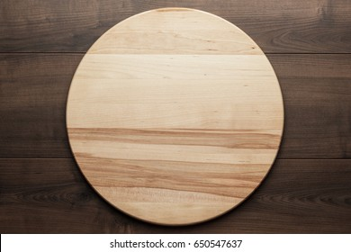 top view of wooden round board for pizza on brown table