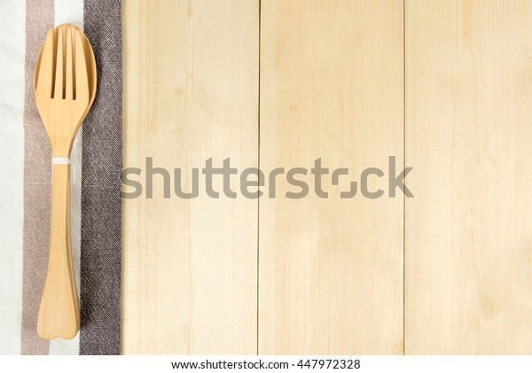 Top view of wooden spoon and fork with napkin on wooden table with copyspace.