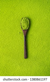 Top view of wooden spoon with green tea Matcha on powder maccha texture background. minimalistic concept.