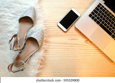 Top view wooden table desk for a fashion blogger on social media. Workspace with white fluffy rag, laptop and feminine accessories. Flat lay.