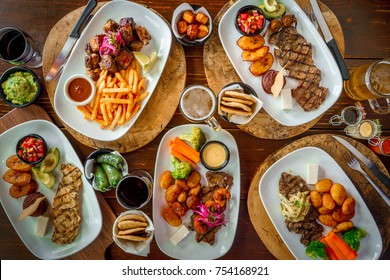Top view of a wooden table full of meat dishes, chicken and appetizers in a restaurant.