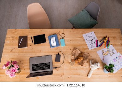 Top view of wooden table with gadgets, pad with stylus, notebooks, cookies, soft toy, pictures, flowerpot, highlighters and roses