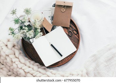 Top view of wooden tray with paper notebook, old photos, candle and spring flowers on white bedding. Relaxing, or working, or writing diary or blog in bed at home.