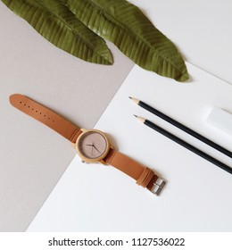 Top view of wooden watch on pastel color background. Artificial leafs, back pencils land leather band watch on soft color background.