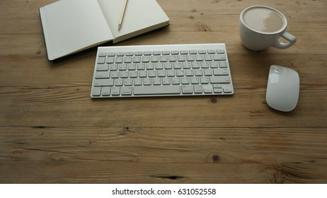 Top view of the wooden working desk with white keyboard and mouse, a cup of latte coffee, a notebook and pencil putting on it. The wood table background is light brown color and  grunge texture
