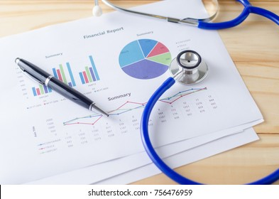 Top view of wooden working table with financial report, stethoscope and pen. Business Concept.