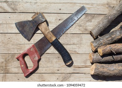 Top view of woodman set of objects such as crossed axe and saw and chopped firewoods in the corner. Flat lay.