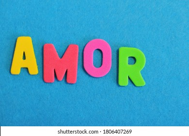 Top view of word  amor lettering on blue background, multicolor letters, textured letters write word amor