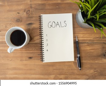 Top view word goals on notebook with pen and coffee over wooden background, business concept with copy space.