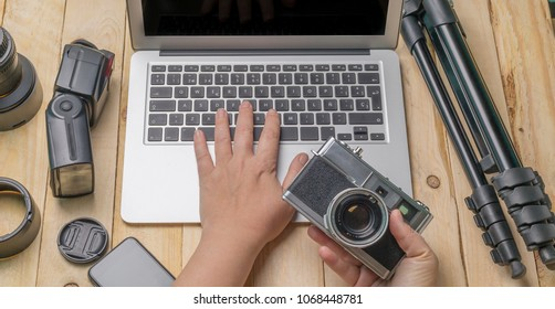 top view of work space photographer and travel concept with camera, drone,flash, computer laptop on wooden background