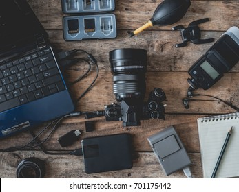 top view of work space photographer with digital camera, battery charger camera, memory card storage box, external harddisk, flash, computer laptop, notebook and camera accessory on wooden background
