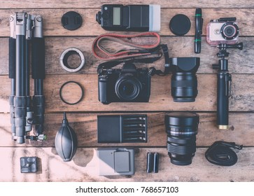 top view of work space photographer with mirrorless camera system, flash, battery charger, cleaning kit, tripod, memory card, and camera accessory on wooden background