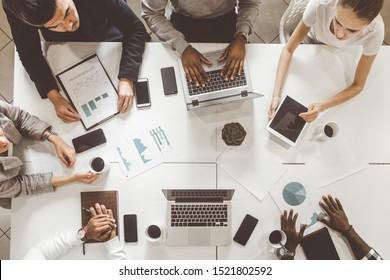 Arbeitsplatz mit Draufsicht. Ein Team junger Büroangestellter, Geschäftsleute mit Laptop arbeiten am Tisch und kommunizieren in einem Büro miteinander. Firmenmanager und Geschäftsführer in einem Meeting. Zusammenarbeit.