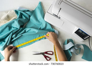 top view of worker measuring green fabric for ready sewing