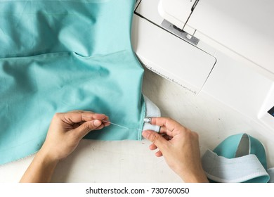 top view of worker sewing fabric by hand