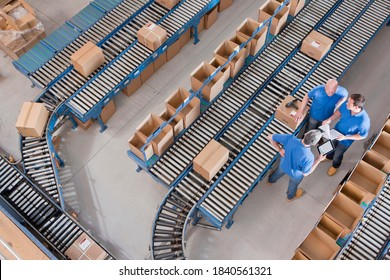 Top view of workers with papers and a digital tablet having a discussion among boxes laid on conveyor belts at a distribution warehouse.