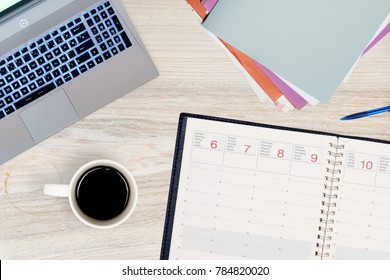 top view of a working desk containing laptop, files,  mug  of coffee, pen and diary with days from monday to friday written in different languages