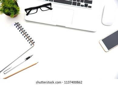 Top view with working desk with laptop,cellphone,notebook pencil coffee cup and eyeglasses in the office.