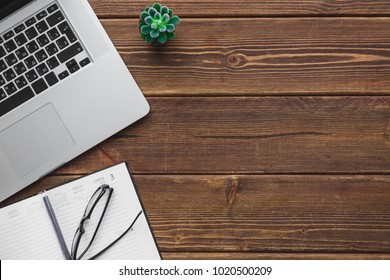 Top view of working place with laptop on wooden table with copy space