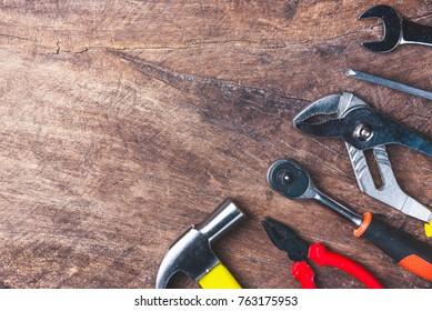 Top view of Working tools,wrench,socket wrench,hammer,screwdriver,plier,electric drill,tape measure,machinist square and safety glasses on wooden background.flat lay design.