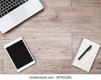 Top view workplace office - White Tablet with blank black screen ,  Laptop computer, notebook on wooden background ( Space and composition for text )