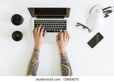 Top view of Workspace with male hands typing on laptop placed on white tabletop with camera lenses, glasses and smartphone